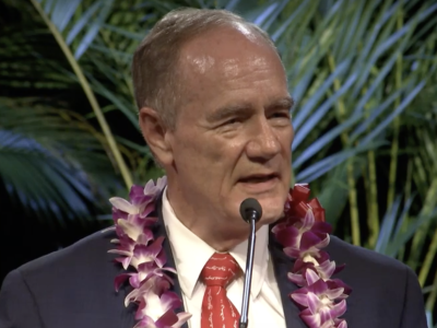 President John S. Tanner speaks wearing a purple and white orchid lei during the devotional