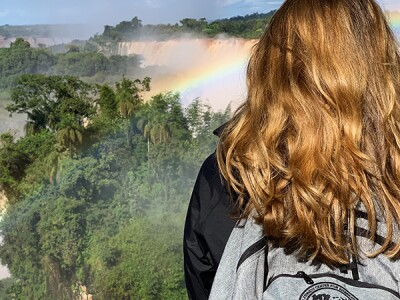 BYU student looks over rainbow and waterfalls while on study abroad