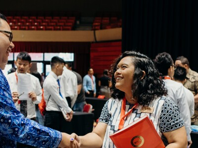 A student shaking hands with an employer at a career conference