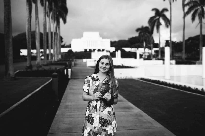 Laura Underwood stands smiling in a black and white photo wearing a tropical leaf and flower-patterned dress holding the Book of Mormon with the Laie Hawaii Temple in the background.
