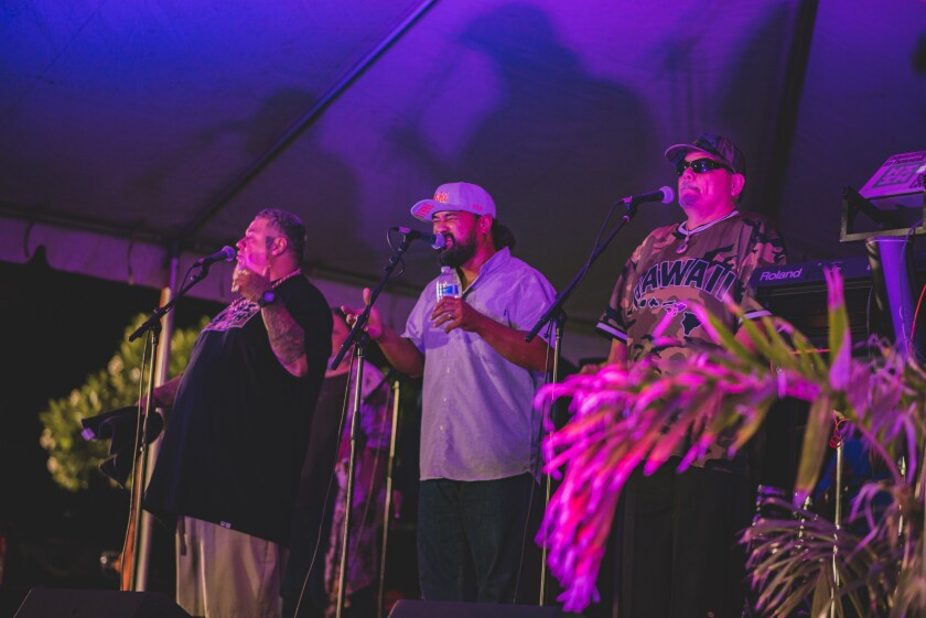 """The three band members in BET sing into the microphones under the purple lights on the stage. They are wearing casual clothing, including a black T-shirt, blue button-up and a camo T-shirt with the word """"Hawaii"""" on it."""