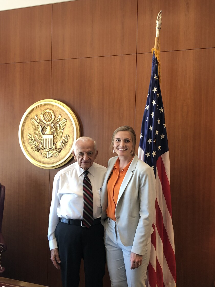 Melissa Jo Townsend and Judge Sam in front of a flag and the seal of the U.S. District Court on a wood paneled wall.