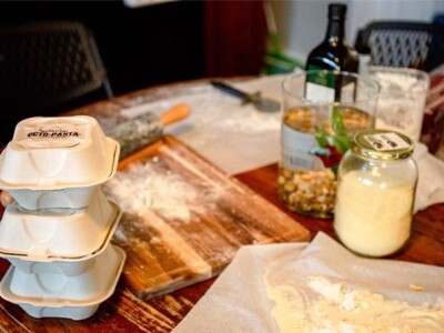 The making of Octo Pasta with carry-out boxes, a cutting board and jars on a table