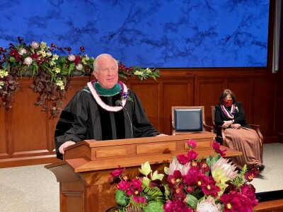 Elder Dyches wearing academic robes at a podium.