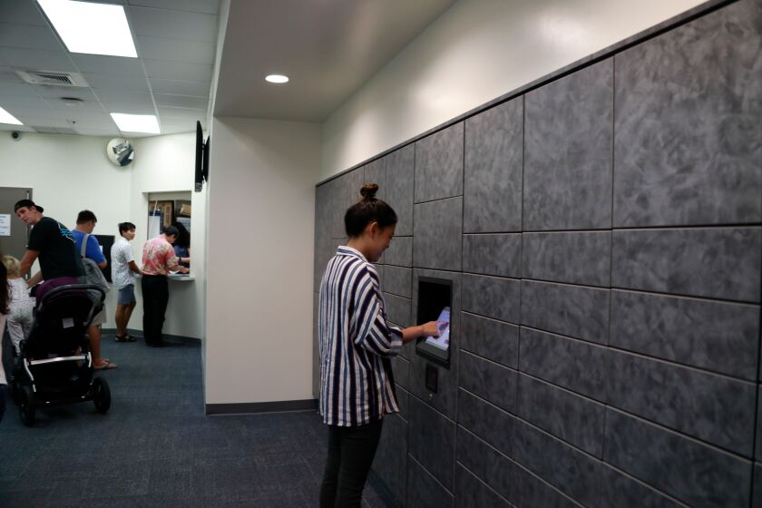 A female student using a touch screen layer on the mail lockers.