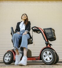 Zaya Altansukh, wearing a white shirt, black jacket, jeans and white shoes in front of the camera, sitting on her red scooter looking up.