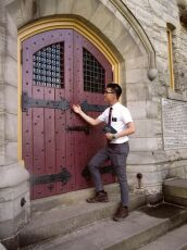 Cheng Hao Leung knocks on a door as a missionary holding a Book of Mormon.