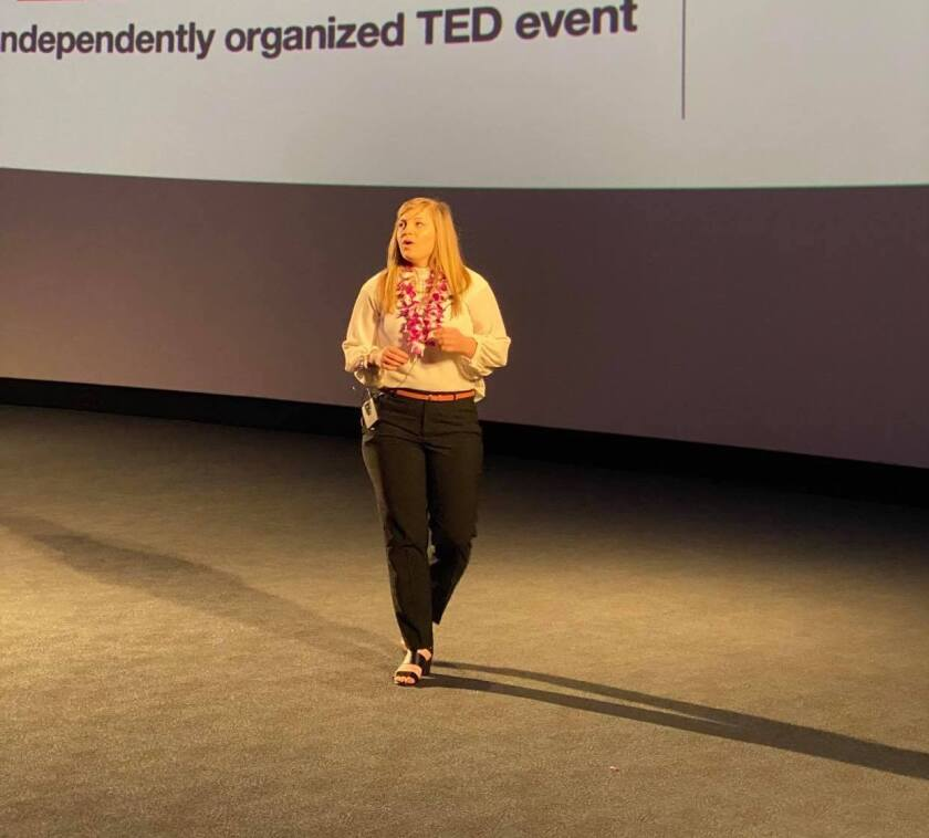 Alison Udall gives her TED talk on stage.