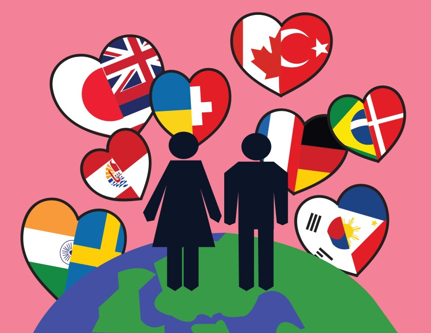 An illustration of a male and a female standing on a globe with hearts filled with flags of different nations.