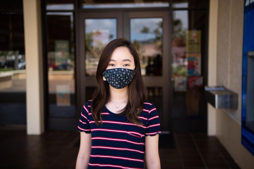 Tania memakai topeng hitam dengan pola kecil dan kemeja bergaris biru, merah dan putih dengan bangunan di belakangnya.
