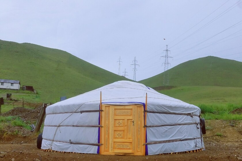 A white mongolian yurt with a light wooden carved door with green hills in the background.