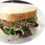 photo of a roast beef sandwich, with tomatoes, onion, spinach on white bread