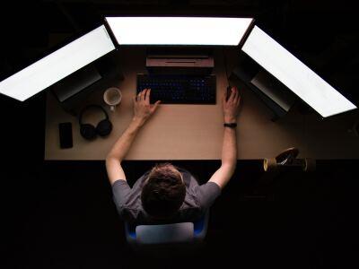 image of man looking at three computer monitors