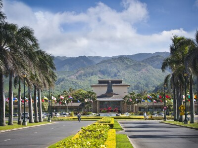 Front entrance of BYU–Hawaii showing the Enter to Learn Go Fort to Serve sign, the Flag Circle, and the McKay Building.