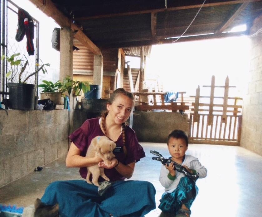 Sister Payne sitting with puppy and little boy in a house in Guatemala.