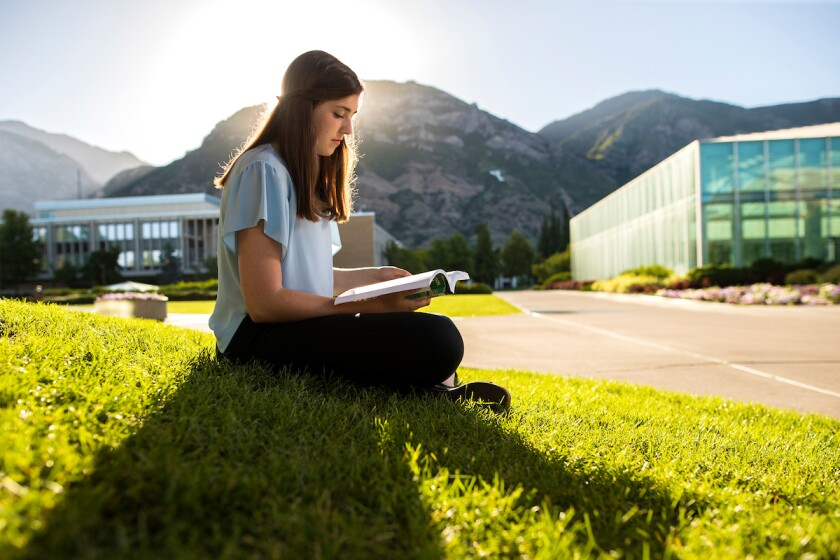 Student sitting on campus reading a book.