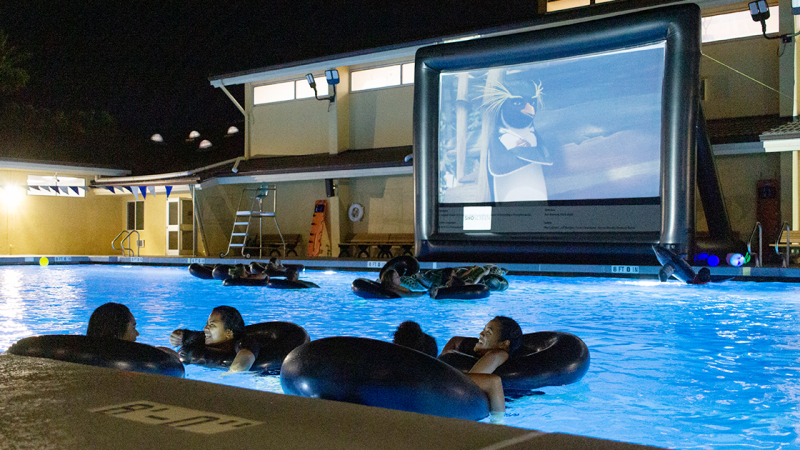 Students use inflatable tubes to watch a movie in the pool on May 31.