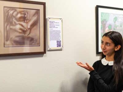 A student gesturing to her Visualizing Learning art exhibit
