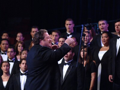 Michael Belnap directing a group of male and female students in concert dresses and tuxedos