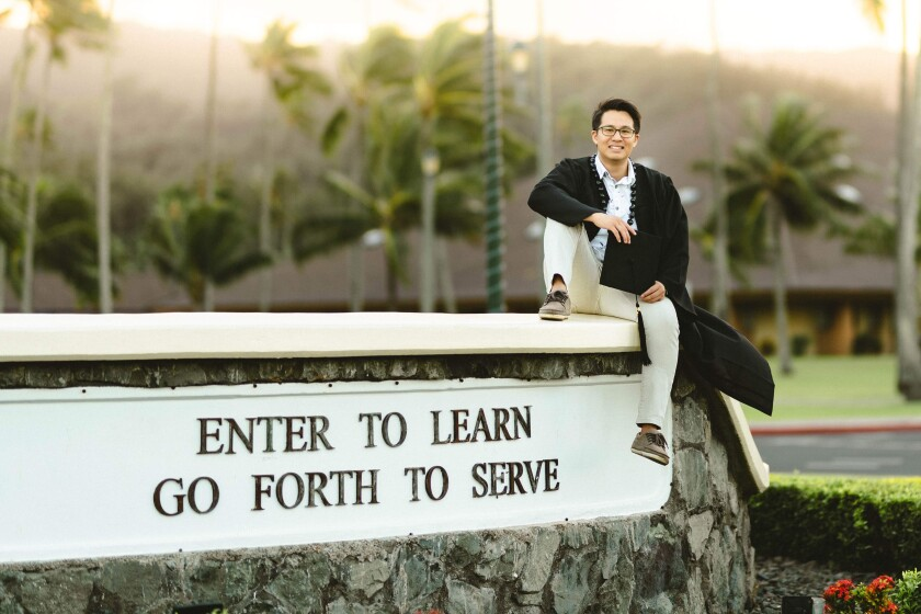 "Winston Lee sits at the entrance of BYUH on the sign that reads ""Enter to Learn, Go Forth to Serve."""