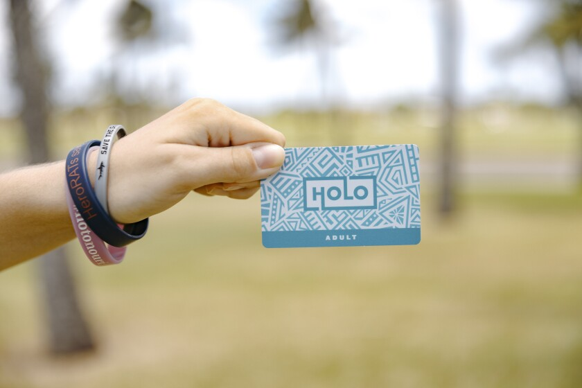"""A hand holding up a blue-designed card saying """"HOLO ADULT"""" with greenery behind it."""