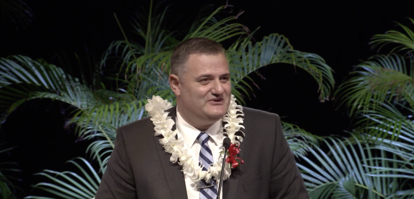 Georgi Lukov stands at the podium in a lei during the devotional