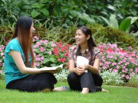 Photo of two female students talking outside on a lawn