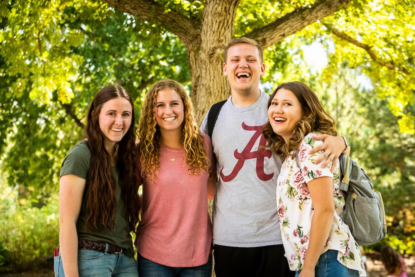 BYU students pose in front of a tree