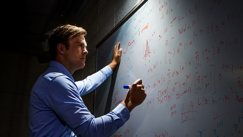 A Graduate  Student working on a problem at a white board.