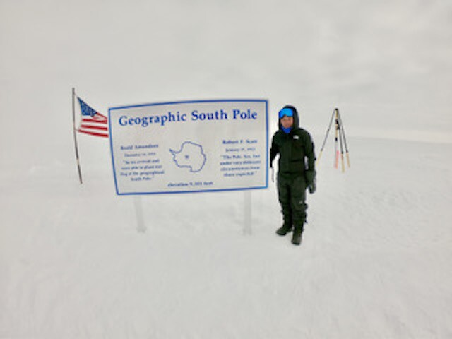 "Spencer Ingley stands at a sign that reads ""Geographic South Pole"" with an American flag in the background"