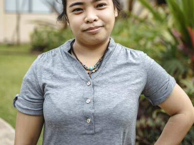 Pristine V. Domingo wears a gray shirt and stands with one hand on her hip.