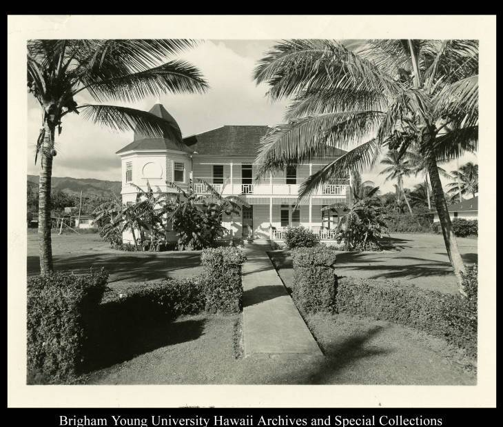 The Victorian-style, two-story Lanihuli House girls dormitory had a two-story hexagon-shaped tower on the front of the house and lanais around the first and second floors. Palm trees are on either side of the house with grass, hedges and more foliage in the front yard.