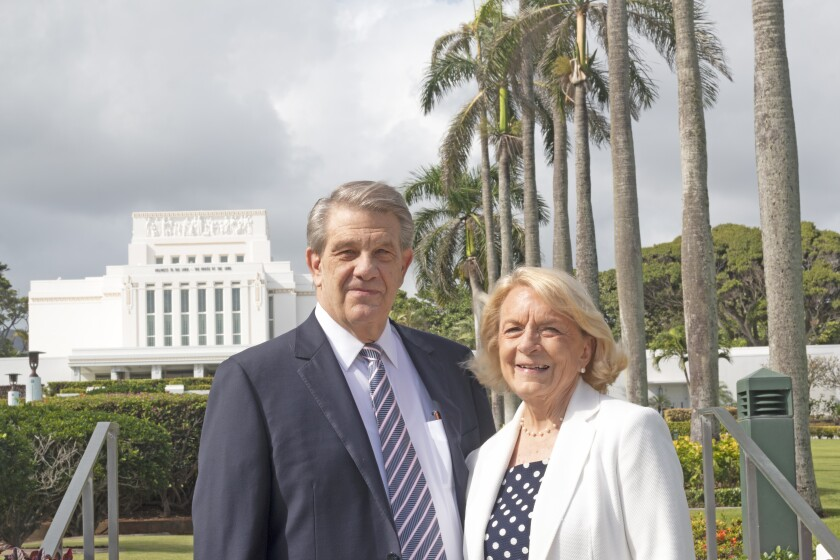 President and Sister Hallstrom smile wearing suits with the Laie Hawaii Temple and palm trees in the background.