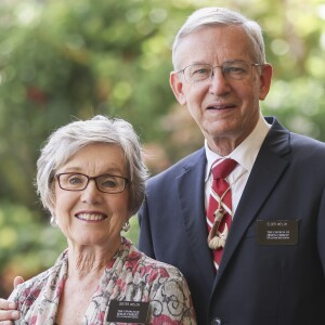A portrait of Elder and Sister Welch smiling at the camera with blurred green plants in the background.