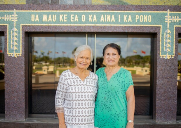 "Ducret and Baker standing together smiling in white skirts Ducret in a white and brown shirt and Baker in a green and blue shirt with a mural wall in the back that says ""UA MAU KE EA O KA AINA I KA PONO."""
