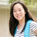 Asian Student smiling with blue backpack.