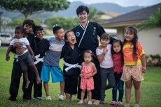 A teacher dressed in a black Hopkido martial arts top and pants is surrounded by nine boys and girls he gives free lessons to on the grass outside of married student housing.
