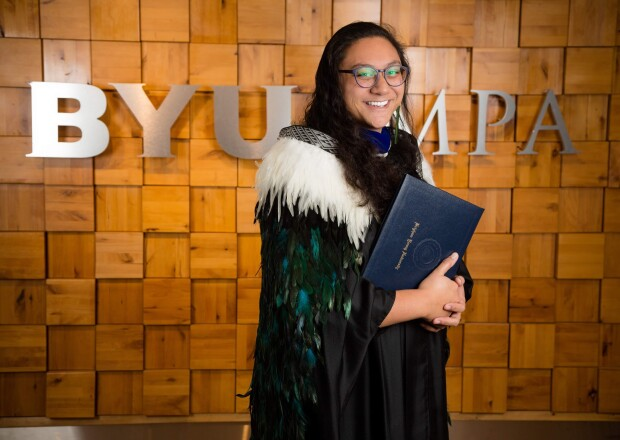 Sala McCarthy-Stonex stands in front of the BYU MPA sign in graduation attire.