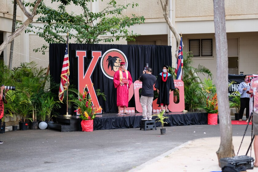A graduate stands on a makeshift graduation stage outside of Kahuku High School.