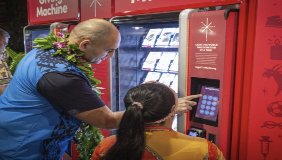 A man stands next to a girl and uses the red Giving Machine to make a donation.