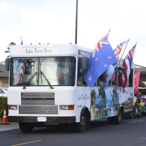 Laie tram with various country flags flying outside of the windows.