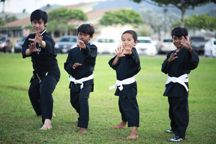 A Hopkido teacher and three young boy students all wearing black tops and pants, strike a martial arts pose on the grass outside of the apartments they live in on campus.