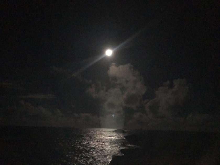 The bright moon in a dark sky over a moon lit ocean