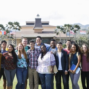 A group of students outside in front of the McKay Classroom Building and Flag Circle.