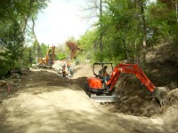 Construction crew digging new stream and trail path on south end of campus.