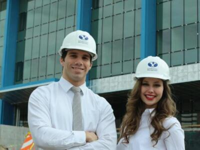 Two Construction Management students in front of a building under construction