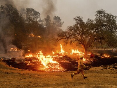 A firefighter runs in front of flames as it burns structures down in a field with heavy smoke coming from it.