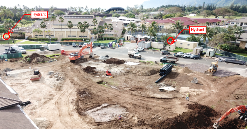 Overall view of the Cafeteria construction area. The site photo is marked on the left to point out hydrants. A fitness center, student dorms, and mountains can be seen beyond the construction area.