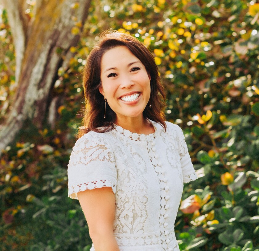Jennifer Kajiyama Tinkham wears a white dress and stands in front of greenery outdoors.