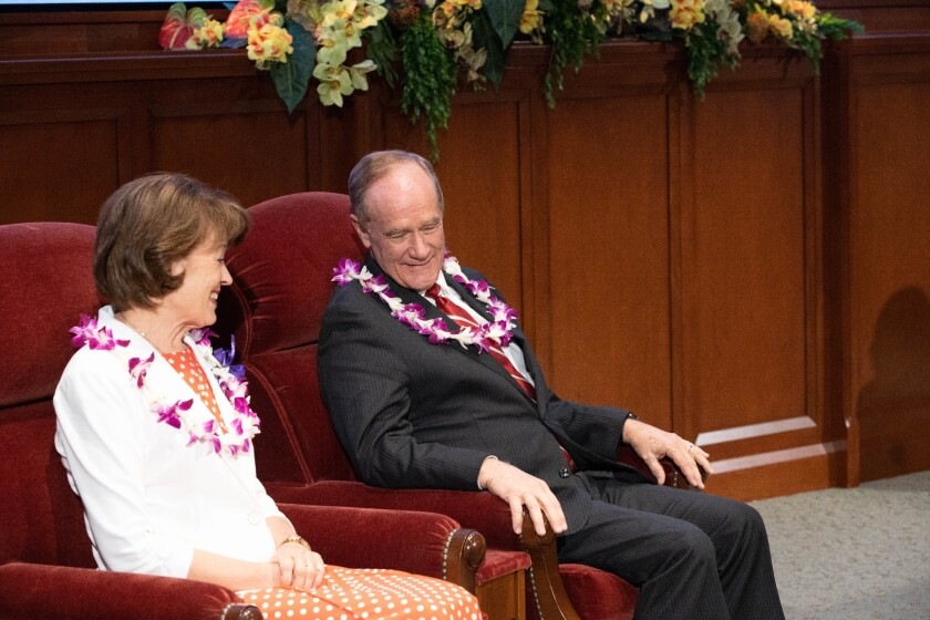 Wearing flower leis, John and Susan Tanner sit beside each other on red chairs.